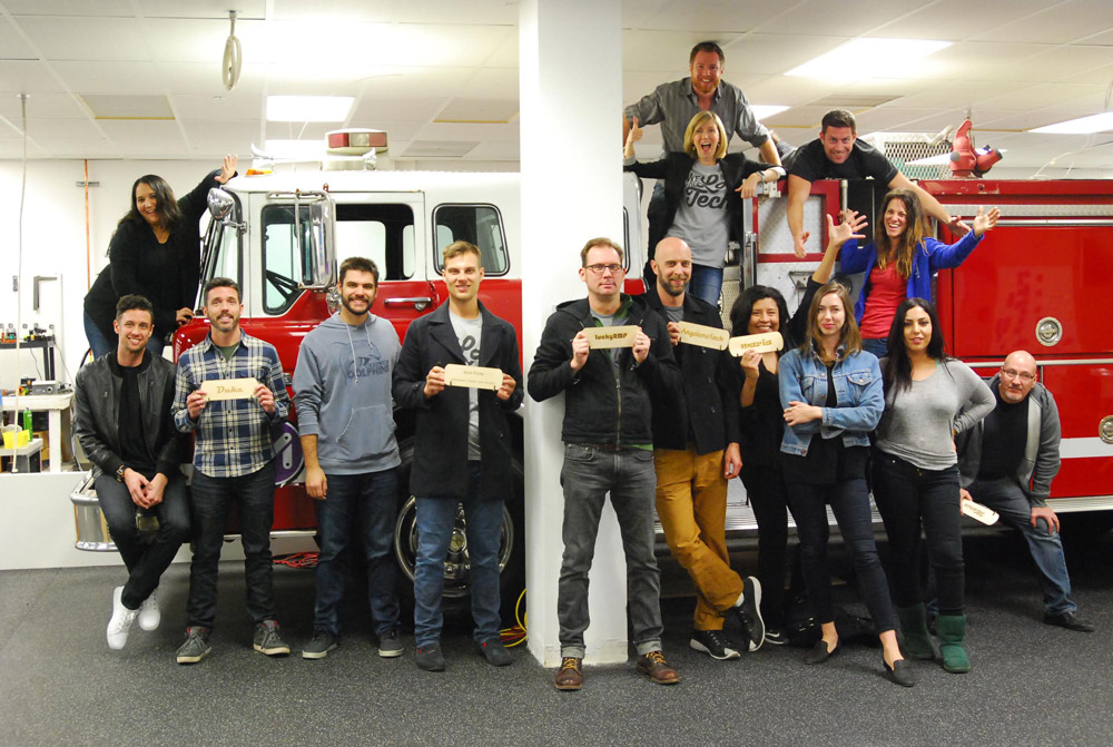 A team at HexLab holding up name plaques