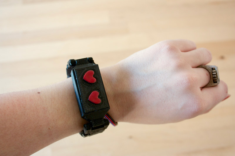 A black bracelet with two love hearts on it